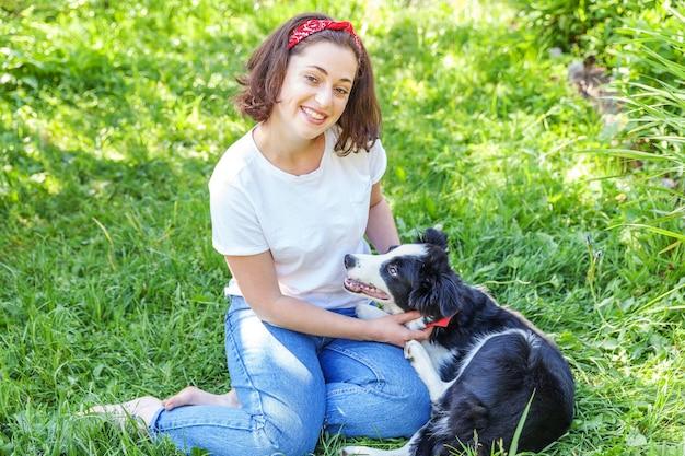 Улыбающаяся молодая привлекательная женщина играет с милым щенком бордер-колли в летнем саду