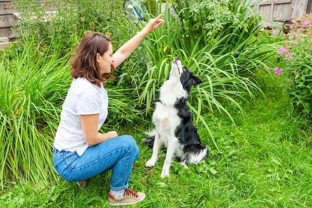 Smiling young attractive woman playing with cute puppy dog border collie in summer garden or city park outdoor