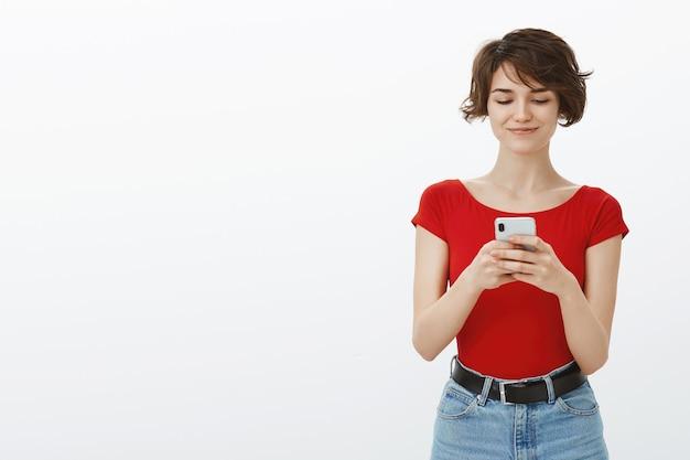 Sorridente giovane donna attraente texting sul cellulare, utilizzando l'app di incontri sullo smartphone