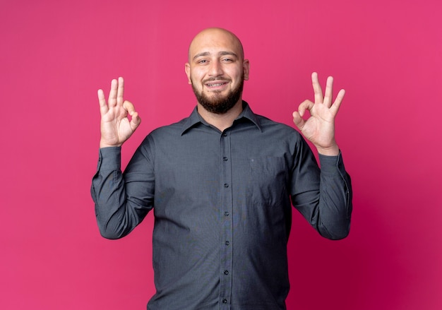 Smiling young bald call center man doing ok signs isolated on crimson wall