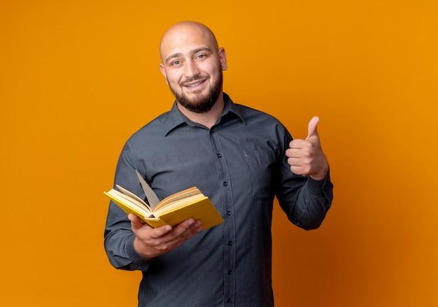 Sorridente giovane uomo calvo call center che tiene libro che mostra pollice in su isolato sulla parete arancione