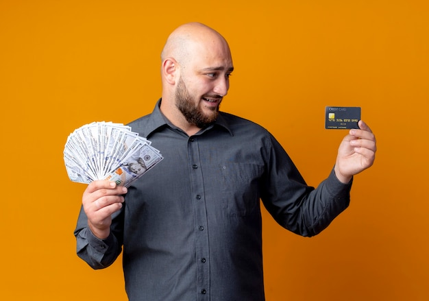 신용 카드와 돈을 들고 오렌지 벽에 고립 된 카드를보고 웃는 젊은 대머리 콜 센터 남자
