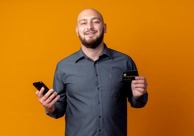 Sorridente giovane uomo calvo call center in possesso di carta di credito e telefono cellulare isolato sulla parete arancione