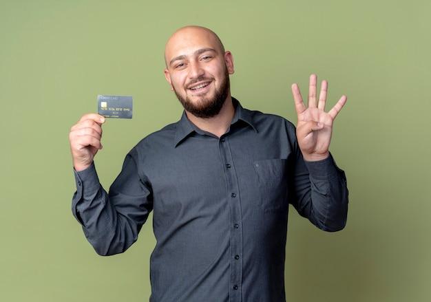 Sorridente giovane uomo calvo della call center che tiene la carta di credito che mostra quattro con la mano isolata sulla parete verde oliva