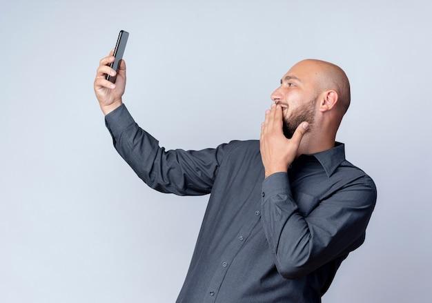 Uomo calvo giovane sorridente della call center che tiene e che esamina il telefono cellulare che mette la mano sulle labbra isolate sulla parete bianca