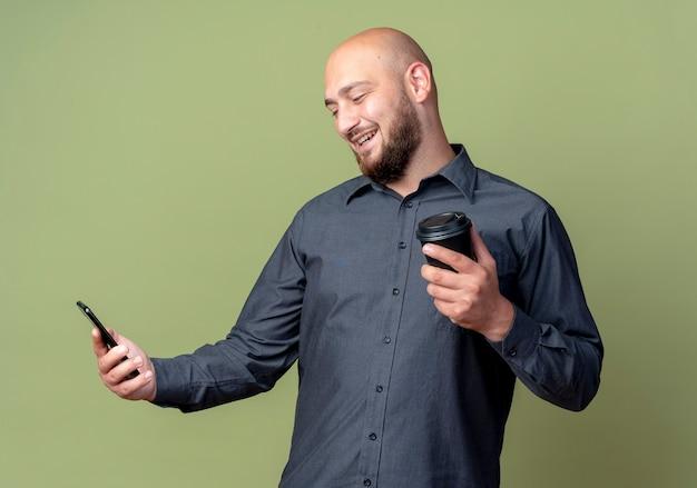 Uomo calvo giovane sorridente della call center che tiene e che esamina il telefono cellulare con la tazza di caffè di plastica in un'altra mano isolata sulla parete verde oliva