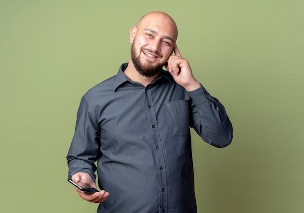 Sorridente giovane uomo calvo della call center che tiene il telefono cellulare che mette il dito sul tempio isolato sulla parete verde oliva