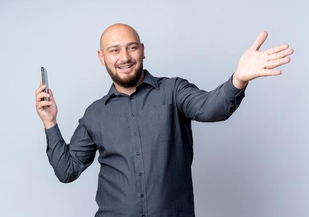 Улыбающийся молодой лысый человек из колл-центра держит мобильный телефон, протягивая руку и глядя в сторону, изолированную на белой стене