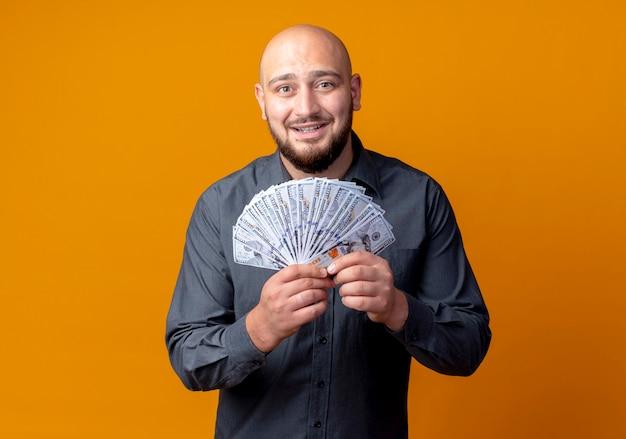 Sorridente giovane uomo calvo call center che tiene soldi isolati sulla parete arancione