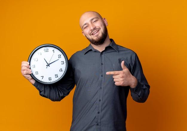Sorridente giovane uomo calvo call center holding e indicando l'orologio isolato sulla parete arancione