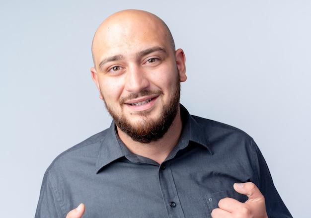 Uomo calvo giovane sorridente del call center che esamina la parte anteriore isolata sulla parete bianca
