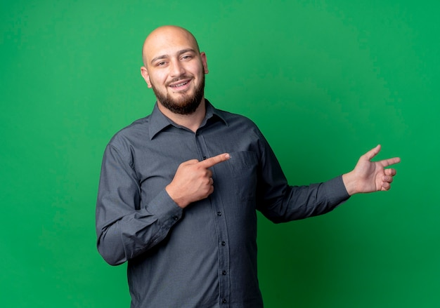 Улыбающийся молодой лысый человек из колл-центра, указывая на сторону, изолированную на зеленой стене