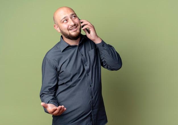 웃는 젊은 대머리 콜 센터 남자 빈 손을 보여주는 올리브 녹색 벽에 고립 된 전화 통화