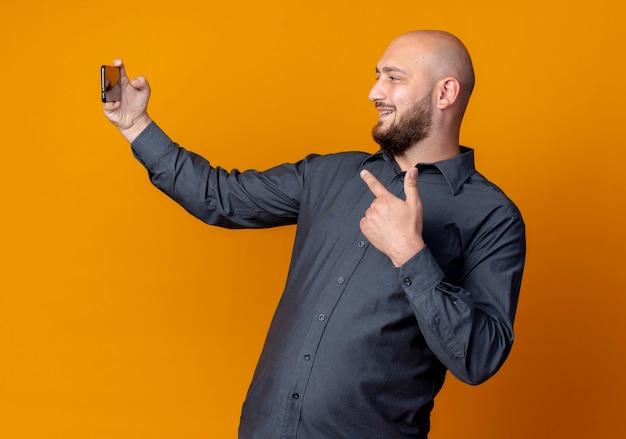 笑顔の若いハゲのコールセンターの男性が自分撮りを取り、オレンジ色の壁に隔離された携帯電話を指しています