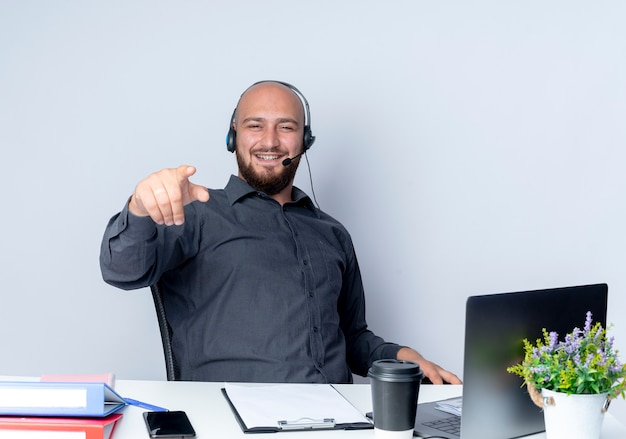 흰 벽에 고립 된 앞에 작업 도구를 가리키는 책상에 앉아 헤드셋을 착용하는 젊은 대머리 콜 센터 남자 미소