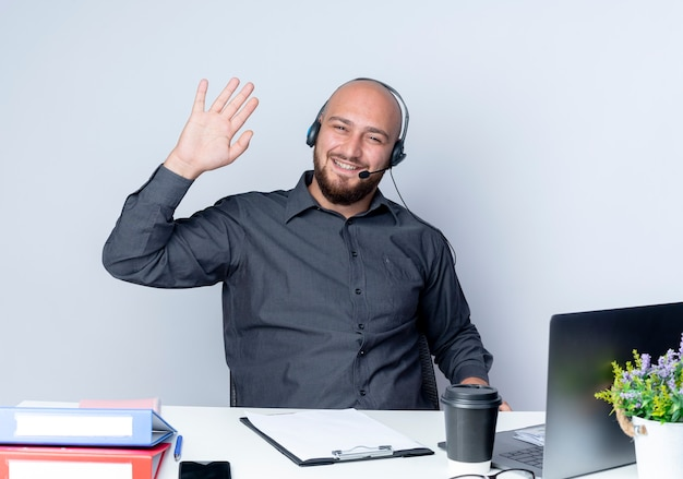 Smiling young bald call center man wearing headset sitting at desk with work tools gesturing hi at front isolated on white wall