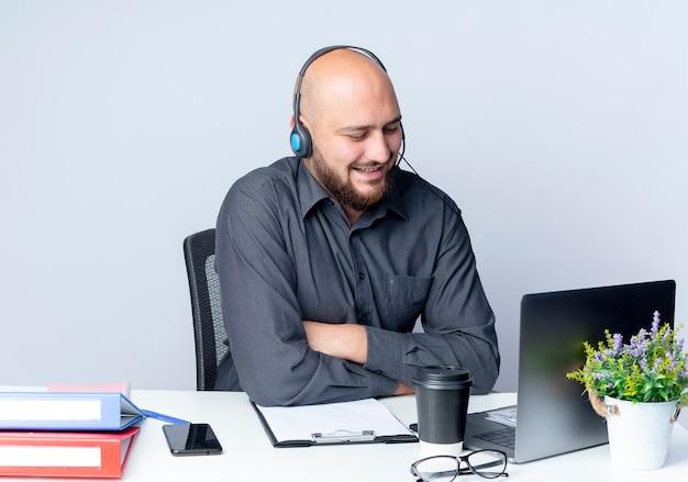 Улыбающийся молодой лысый человек в колл-центре в гарнитуре сидит с закрытой позой за столом с рабочими инструментами, глядя на ноутбук, изолированный на белой стене