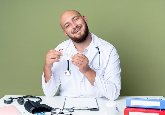 녹색 벽에 고립 된 약을 들고 의료 도구와 책상 작업에 앉아 의료 가운과 청진기를 입고 웃는 젊은 대머리 남성 의사