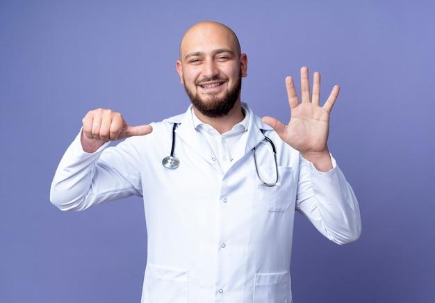 의료 가운과 청진기를 입고 웃는 젊은 대머리 남성 의사 무료 사진