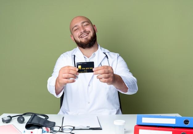 Sorridente giovane medico maschio calvo che indossa tunica medica e stetoscopio seduto alla scrivania