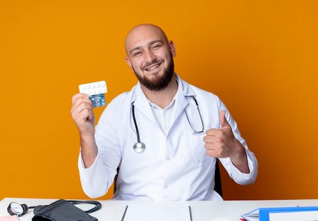 Sorridente giovane maschio calvo medico indossando abito medico e stetoscopio seduto alla scrivania con strumenti medici tenendo le pillole il suo pollice in alto isolato su sfondo arancione