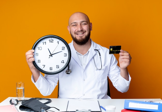 Smiling young bald male doctor wearing medical robe and stethoscope sitting at work desk with medical tools holding wall clock and credit card isolated on orange background