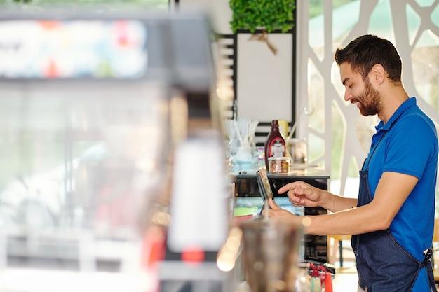 Улыбающийся молодой бариста, использующий кассовый аппарат и ввод данных онлайн-заказа