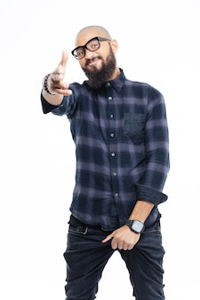 Smiling young bearded african man in glasses standing and pointing