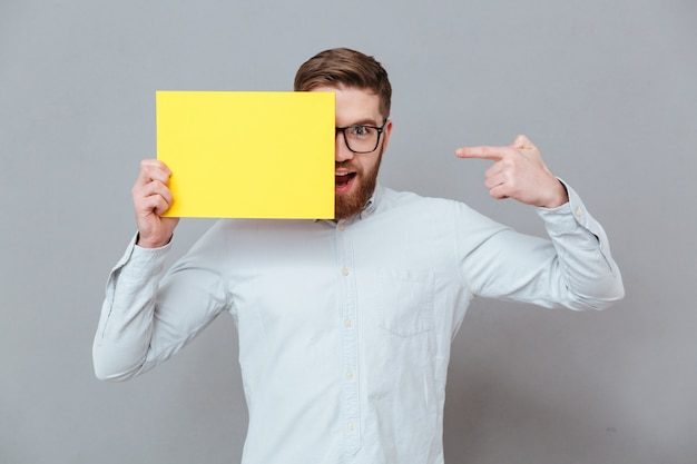 Улыбающийся молодой бородатый бизнесмен, держа чистый лист бумаги