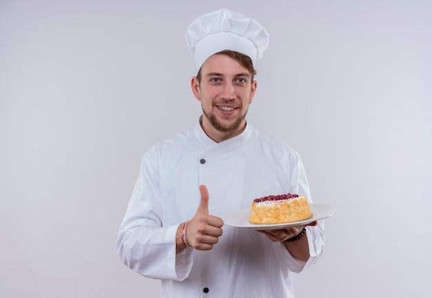 Un sorridente giovane chef barbuto uomo che indossa l'uniforme bianca del fornello e cappello che tiene un piatto con la torta e che mostra i pollici in su mentre osserva su un muro bianco