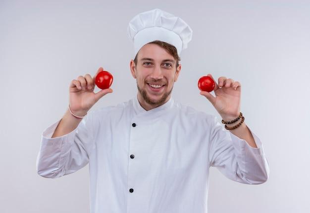 Un giovane uomo barbuto sorridente del cuoco unico che porta l'uniforme bianca del fornello e cappello che tengono i pomodori rossi mentre osservava su un muro bianco