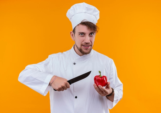 A smiling young bearded chef man in white uniform cutting red bell pepper with knife while looking on an orange wall