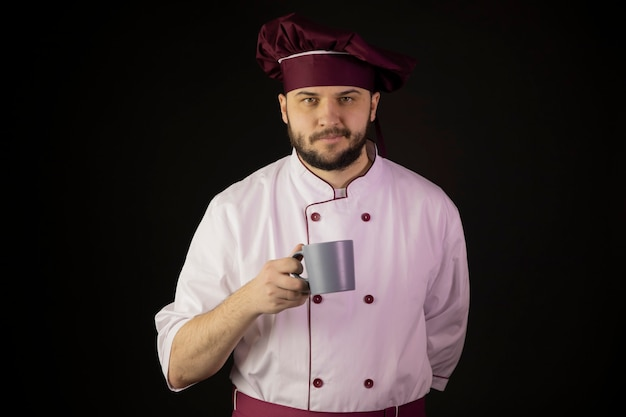 Smiling young bearded male chef in uniform holding coffee cup in his hand