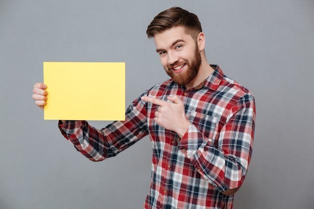 Giovane uomo barbuto sorridente che tiene carta in bianco