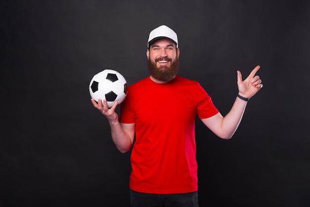 Улыбающийся молодой бородатый мужчина в красной футболке держит футбольный мяч и указывает в сторону