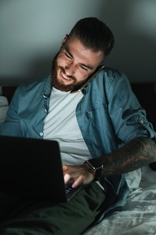 Smiling young bearded man laying on bed at home at night, talking on mobile phone while working on laptop computer