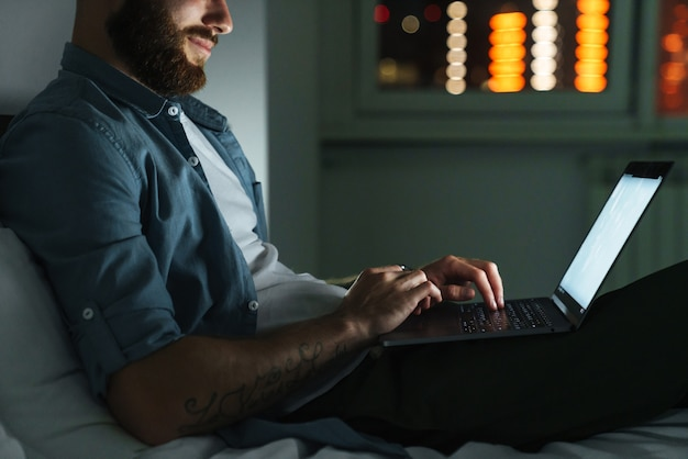 Smiling young bearded man laying on bed at home at night, working on laptop computer