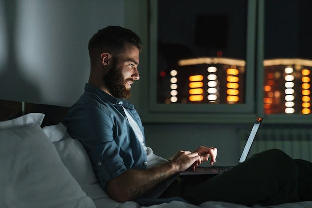 Улыбающийся молодой бородатый мужчина, лежа на кровати дома ночью, работая на портативном компьютере