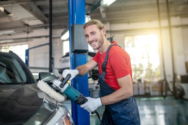 ガレージで特別なブラシで灰色の車を専門的に磨く若いひげを生やした男の笑顔