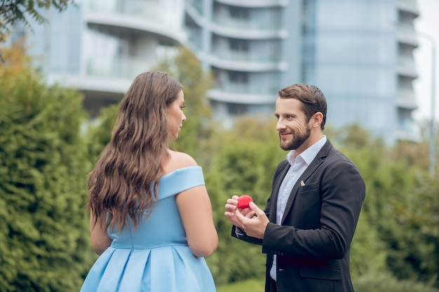 Smiling young bearded man with red small case in hands and serious woman in blue dress standing opposite each other