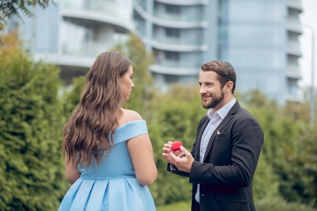 Улыбающийся молодой бородатый мужчина с красным футляром в руках и серьезная женщина в синем платье стоят друг напротив друга