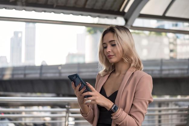 공식적인 유니폼 확인 회의 일정을 확인하고 도시에서 운송하는 동안 스마트 폰에서 기업 앱을 사용하여 채팅을 하고 웃고 있는 젊고 아름다운 미국 비즈니스 여성. 기쁨의 얼굴을 가진 행복한 일하는 여성.