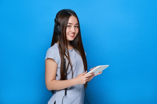 Smiling young beautiful asian girl listening to music on headphones and holds tablet on blue wall