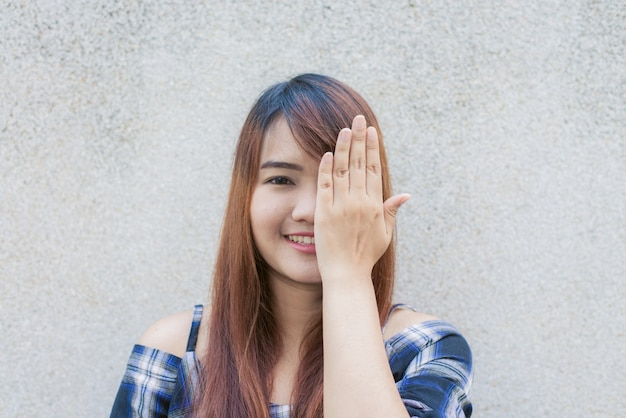 Smiling young beautiful asian woman closing her eyes with hands on concrete wall background. vintage effect style pictures.smiling young beautiful asian woman closing her eyes with hands on concrete wall background. vintage effect style pictures.