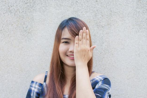 Sonriendo joven hermosa mujer asiática cerrar los ojos con las manos en el fondo de muro de hormigón. vintage efecto de estilo pictures.miling joven hermosa mujer asiática cerrar los ojos con las manos en el fondo de muro de hormigón. vintage efecto estilo imágenes.