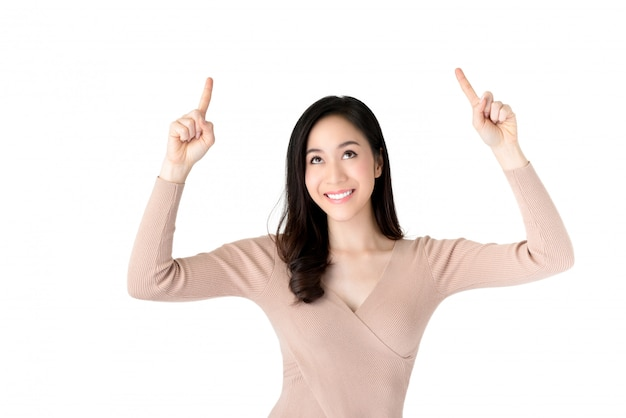 Smiling young beautiful asian woman looking and pointing her hands up