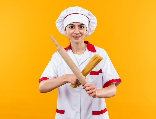 Sorridente giovane bella ragazza in uniforme da chef che tiene e attraversa gli spaghetti con il mattarello