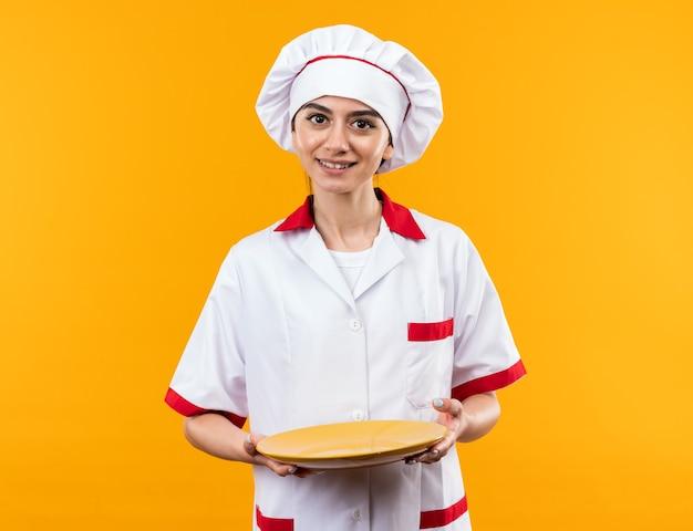 Sorridente giovane bella ragazza in uniforme da chef che tiene piatto