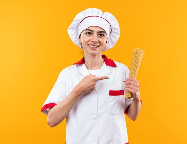 Sorridente giovane bella ragazza in uniforme da chef che tiene e indica gli spaghetti