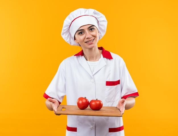 Sorridente giovane bella ragazza in uniforme da chef che tiene i pomodori sul tagliere